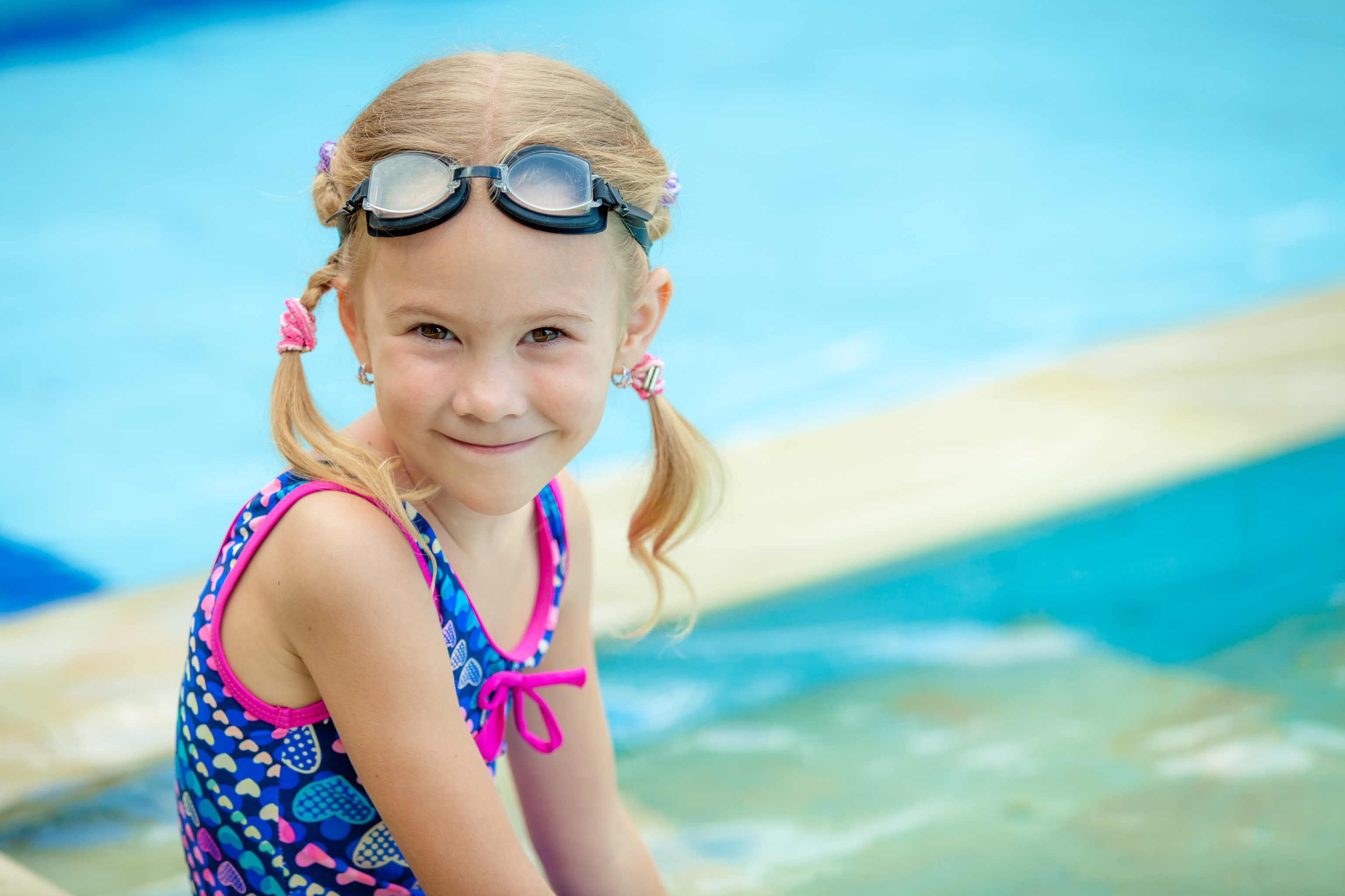 little girl sitting near swimming pool