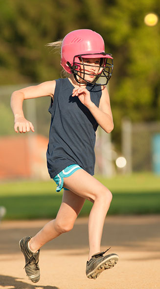 girl in baseball helmet running