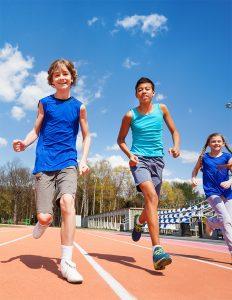 Three kids running on a track