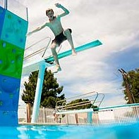 Boy jumping off climbing wall into the pool