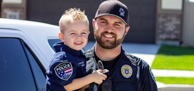 Police officer holding a boy in a police uniform.